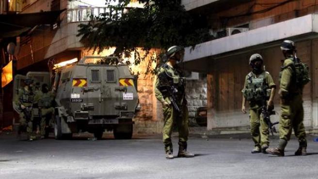 Soldados de Israel patrullan las calles de Hebrón tras el secuestro tres estudiantes israelíes.