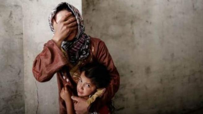 Una mujer coge a su hija mientras la aviación siria bombardea un barrio cercano a su casa.