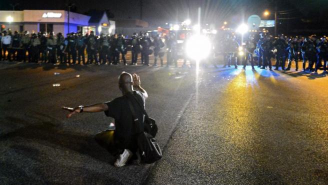 Agentes de la Policía vigilan las protestas en contra de la muerte del joven Michael Brown en Ferguson (Estados Unidos). El gobernador del Estado de Misuri, en el medio oeste de EE UU, Jay Nixon, movilizó a la Guardia Nacional ante los continuos disturbios tras la muerte de un joven negro desarmado en la localidad de Ferguson por un policía blanco que, según datos de una autopsia divulgados, le disparó seis veces.