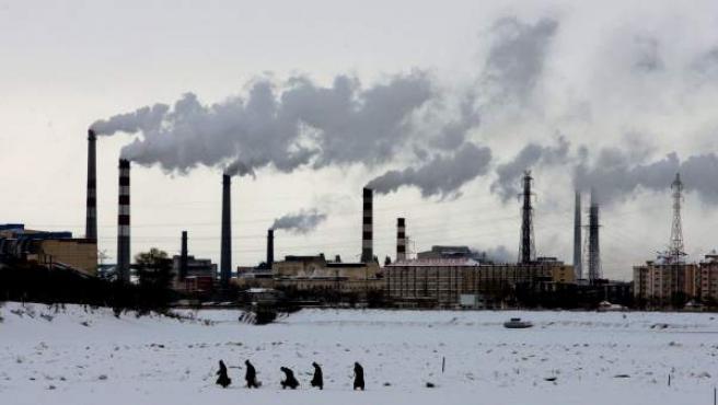 Varios ciudadanos chinos caminan sobre las aguas heladas del río Songhua, frente a una fábrica que está emitiendo gases en la localidad china de Jiamusi.