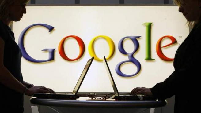 Dos personas navegan con su portátil con el logotipo de Google al fondo.