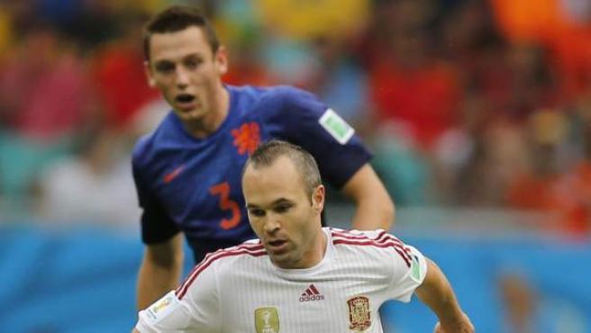 El centrocampista español Andrés Iniesta (d) avanza con el balón perseguido por el defensa holandés Stefan de Vrij (detrás).