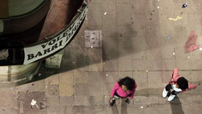 Dos mujeres ofrecen sus servicios sexuales en una calle de Barcelona bajo una pancarta en la que se puede leer 'Queremos un barrio digno'.