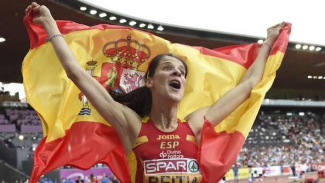 La saltadora cántabra Ruth Beitia celebra con la bandera de España su victoria en la prueba de salto de altura.