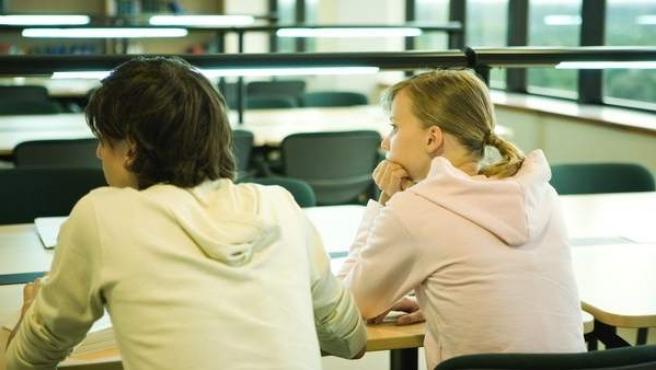 Dos jóvenes estudiantes, en una clase escolar.