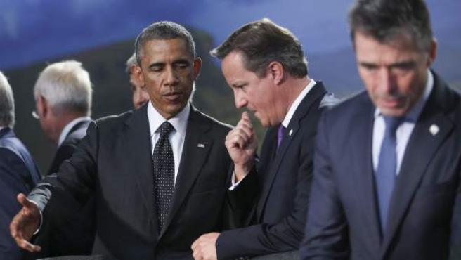El presidente de EE UU, Barack Obama (izda.), y el primer ministro del Reino Unido, David Cameron, hablan durante la cumbre d ela OTAN.