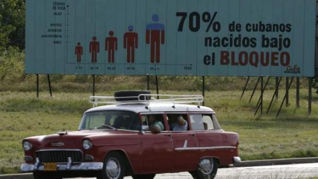 """Un coche antiguo pasa junto a un cartel que reza """"70% de cubanos nacidos bajo el bloqueo"""", en referencia al embargo de EE UU a Cuba."""