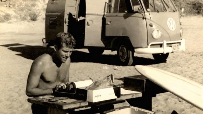 Severson redactando un artículo a pie de playa junto a su tabla de surf y su furgoneta en 1959