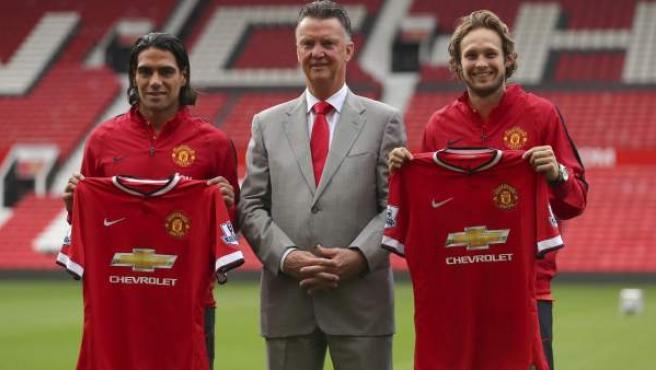 Los futbolistas Radamel Falcao y Daley Blind posan junto a Louis Van Gaal en su presentación como jugadores del Manchester United.