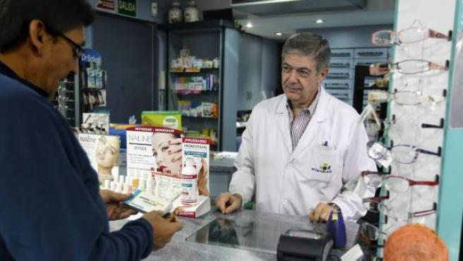 Un cliente compara un medicamento en la farmacia.