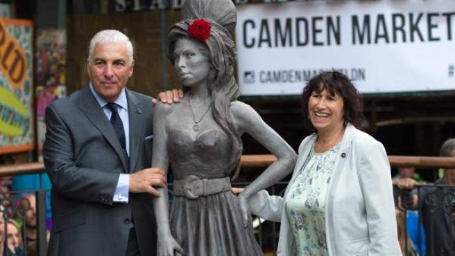El padre de la cantante posa junto a la estatua de su hija en el barrio de Camden, en Londres.