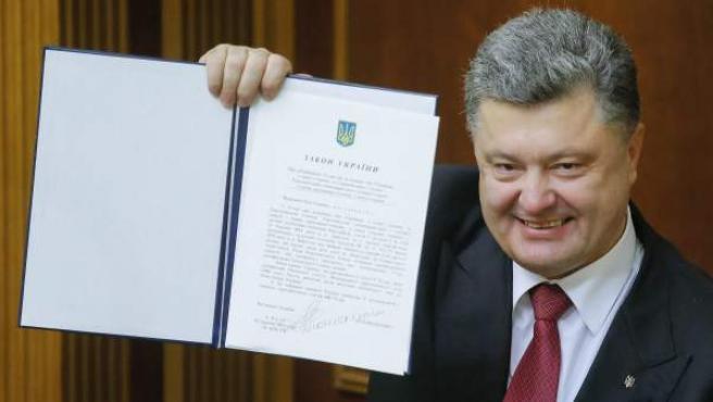 El presidente ucraniano, Petro Poroshenko, muestra el documento de ratificación del Acuerdo de Asociación con la Unión Europea (UE) después de firmarlo en la Rada Suprema en Kiev (Ucrania).