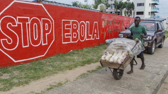 Un hombre lleva pan junto a un muro en con un anuncio de la campaña creada para combatir el brote de ébola en África Occidental, en Monrovia, Liberia.