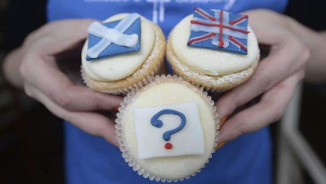 La empleada de una pastelería posa sujetando una madalena decorada con un interrogante junto a otras dos con la bandera de Escocia (arriba, i) y la del Reino Unido, en Edimburgo (Escocia).