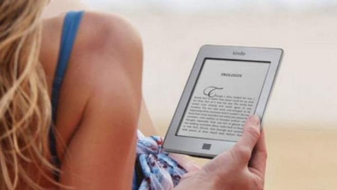 Una chica lee un libro electrónico en el 'e-reader' Kindle.