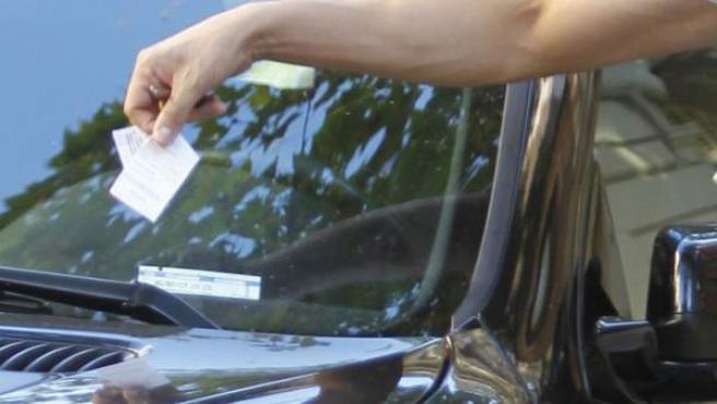 Un hombre retirando una multa de aparcamiento de su coche.