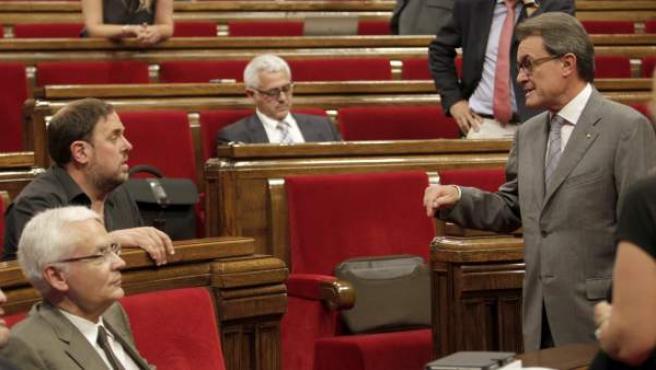 El líder de ERC, Oriol Junqueras, y el presidente de la Generalitat, Artur Mas, conversan en el hemiciclo del Parlamento catalán.