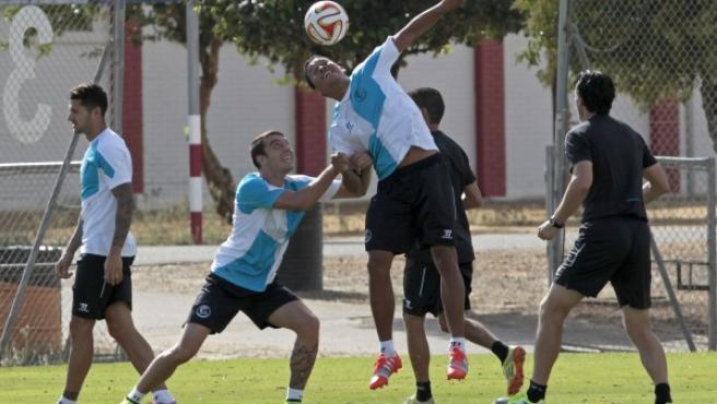 El entrenador del Sevilla, Unai Emery (d), observa a sus jugadores Iborra (I), Iago Aspas (2I) y Carlos Bacca (C), durante el entrenamiento.