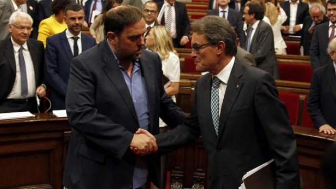 El presidente de la Generalitat, Artur Mas (d), estrecha la mano del líder de ERC, Oriol Junqueras, tras aprobarse en el Parlamente la Ley de Consultas.