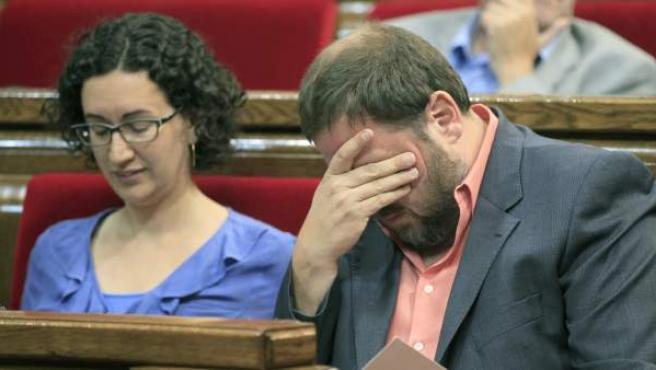 El presidente de ERC, Oriol Junqueras, se frota la cara durante un pleno del Parlamento de Cataluña junto a la número 2 del partido, Marta Rovira.