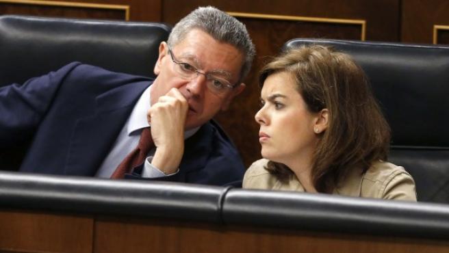 El ministro de Justicia, Alberto Ruiz-Gallardón (i), conversa con la vicepresidenta del Gobierno, Soraya Sáenz de Santamaría (d), en el pleno del Congreso de los Diputados.