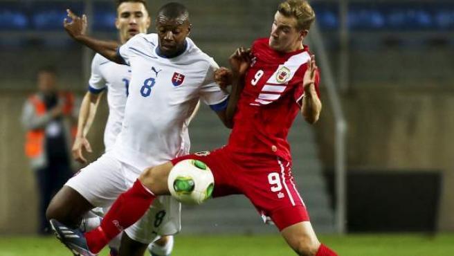 Adam Priestley, jugador de la selección de Gibraltar, pelea la posesión del balón con el eslovaco Karim Guede.
