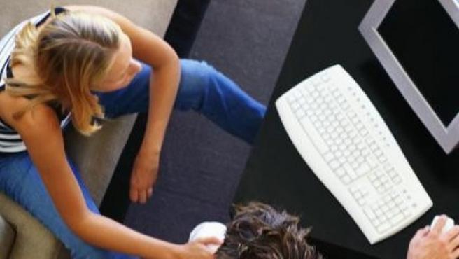 Dos jóvenes usan un ordenador.