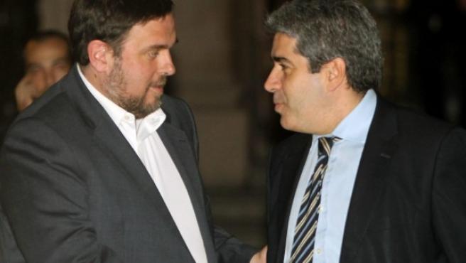 El portavoz del Govern, Francesc Homs (d) y el líder de ERC, Oriol Junqueras (i), se saludan a la salida de la reunión celebrada en la Generalitat, tras cerrar finalmente un acuerdo de gobernabilidad y estabilidad parlamentaria en Cataluña.