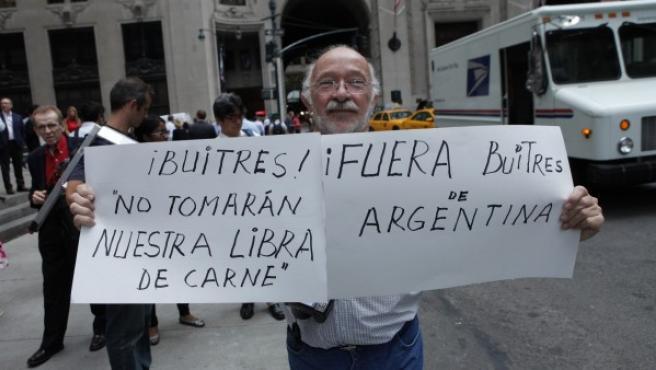 Un argentino sostiene un cartel de denuncia a la salida del ministro de Economía argentino, Axel Kicillof, en el consulado de Argentina en Nueva York (EEUU)