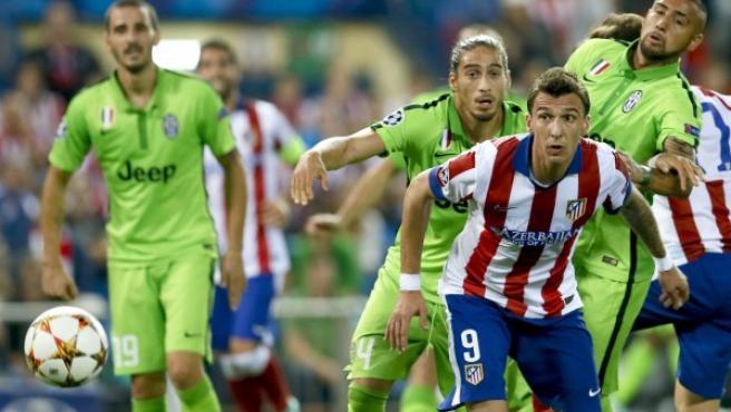 El delantero croata del Atlético de Madrid Mario Mandzukic (2d) persigue el balón junto al uruguayo Martín Cáceres (3d) y el chileno Arturo Vidal (d), de la Juventus, durante el partido de la segunda jornada de la fase de grupos de la Liga de Campeones.