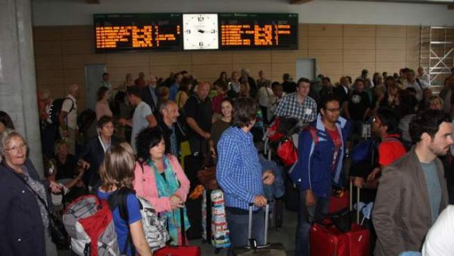 Decenas de pasajeros aguardan a que llegue algún autocar en el vestíbulo de la estación del AVE de Girona.