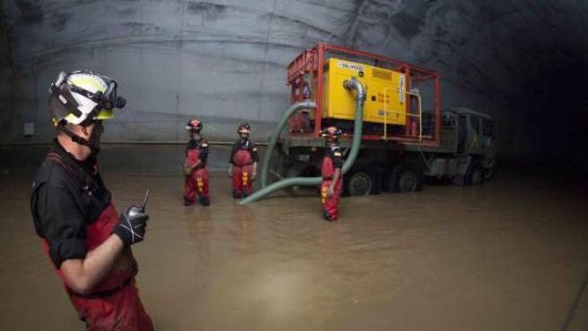Efectivos de la Unidad Militar de Emergencias (UME) trabajan en el túnel del AVE inundado en Girona.