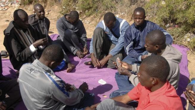 Varios inmigrantes juegan a las cartas, en el Centro de Estancia Temporal de Inmigrantes (CETI), colapsado tras la entrada a Melilla de casi medio millar de inmigrantes.