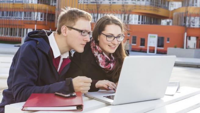 Dos jóvenes atentos a un ordenador.