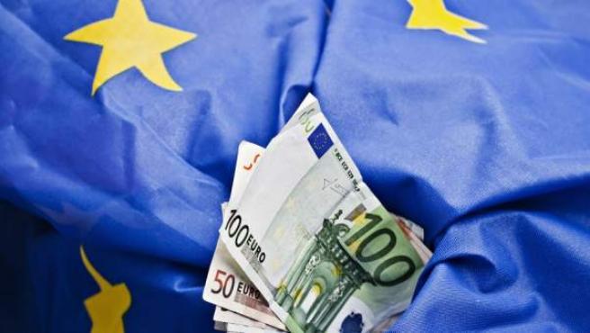Varios billetes de euro sobre una bandera.