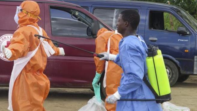 Miembros de la Cruz Roja de Sierra Leona desinfectan el área después de recuperar los cuerpos de una mujer de 80 años y nieta que se cree murieron a causa del virus Ébola.