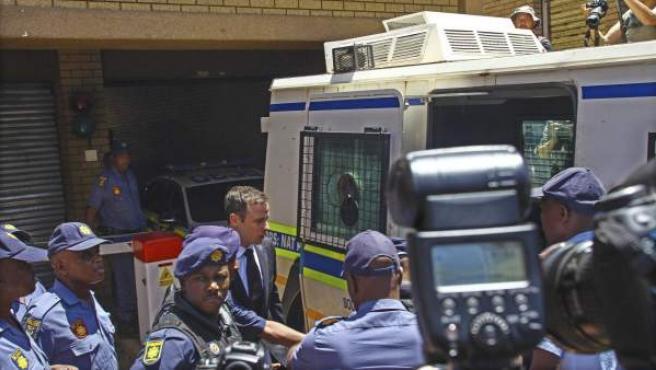 El atleta paralímpico sudafricano Oscar Pistorius (c) es entroducido en un furgón policial a su salida del Tribunal Superior de Pretoria (Sudáfrica).