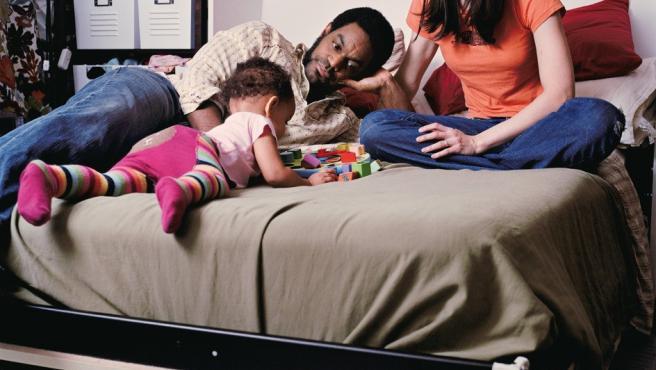 Daria y Cedrid juegan en cama con su primer hijo
