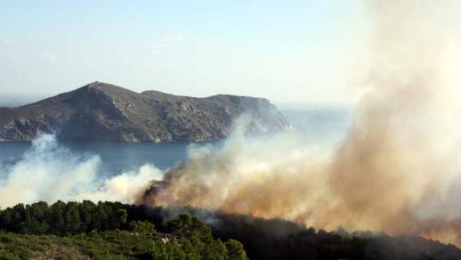 La columna de humo que genera el incendio declarado este miércoles en el Cap de Creus (Girona) y que avanza hacia la Cala Montjoi.