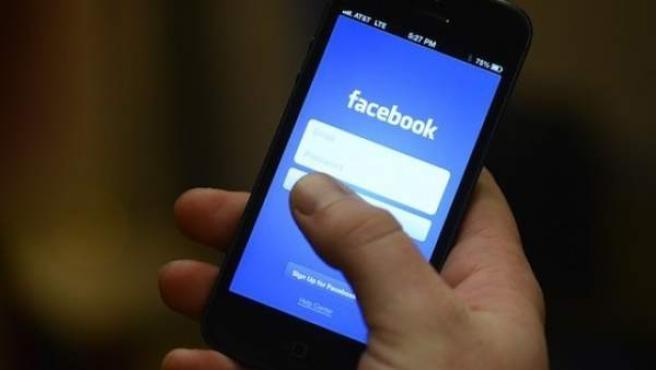 Una persona utilizando Facebook en su smartphone.