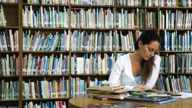 Una mujer consultando unos libros en una biblioteca.