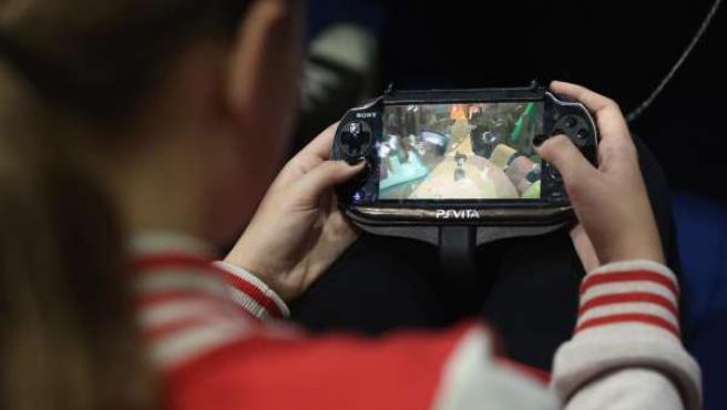 Niña juega con dispositivo móvil, videojuego