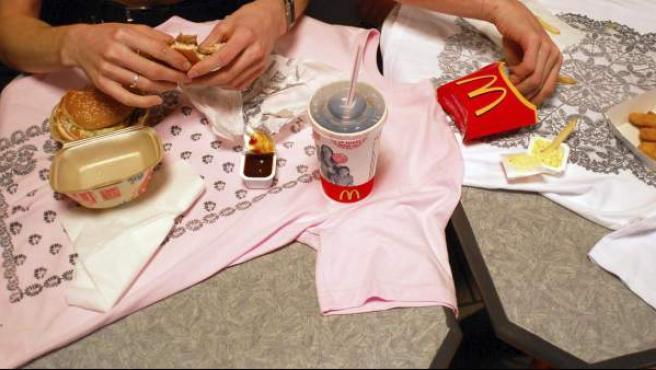 Jóvenes comiendo hamburguesas y patatas de McDonald´s.
