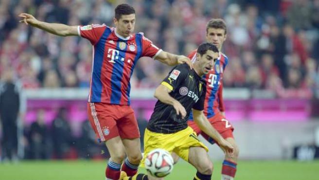 El delantero polaco del Bayern de Múnich Robert Lewandowski pelea un balón con el centrocampista armenio del Borussia de Dortmund Henrikh Mkhitaryan.