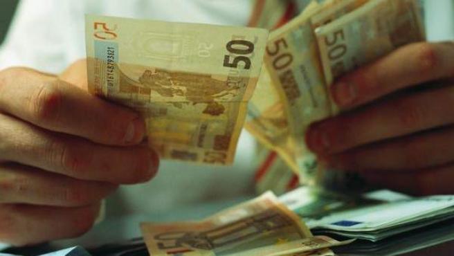 Un hombre cuenta billetes de 50 euros.