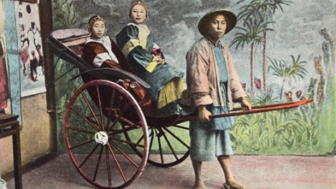 Postal de comienzos del siglo XX de dos jóvenes chinas montadas en una 'jinrikisha'