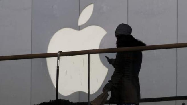 Una chica camina utilizando su móvil frente a un edificio con el logo de Apple.
