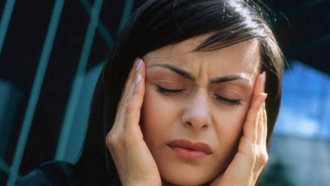 Una mujer se lleva las manos a la cabeza, uno de los gestos más usuales entre personas que sufren migrañas.