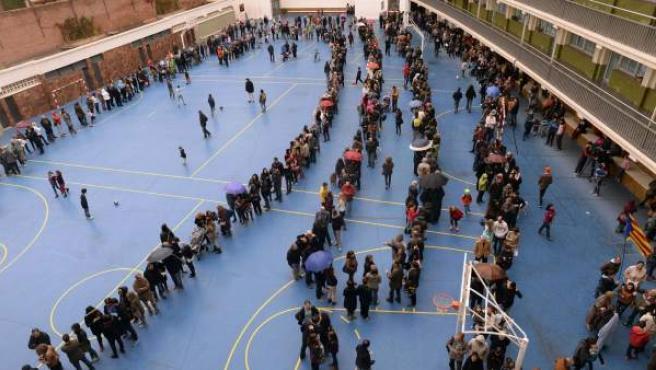 Numerosas personas hacen cola en un instituto de Barcelona para votar en el proceso participativo de este 9-N.