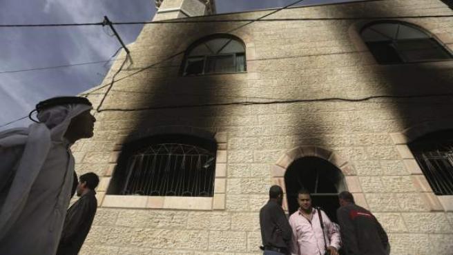 Varios palestinos inspeccionan los daños registrados en una mezquita de la localidad cisjordana de Al Mughayir tras haber sido supuestamente incendidada.